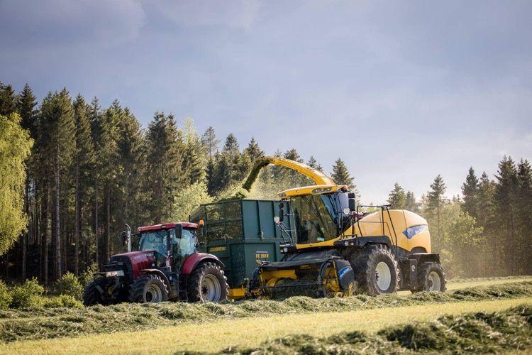 Traktorer arbetar med vallskörd på fält.