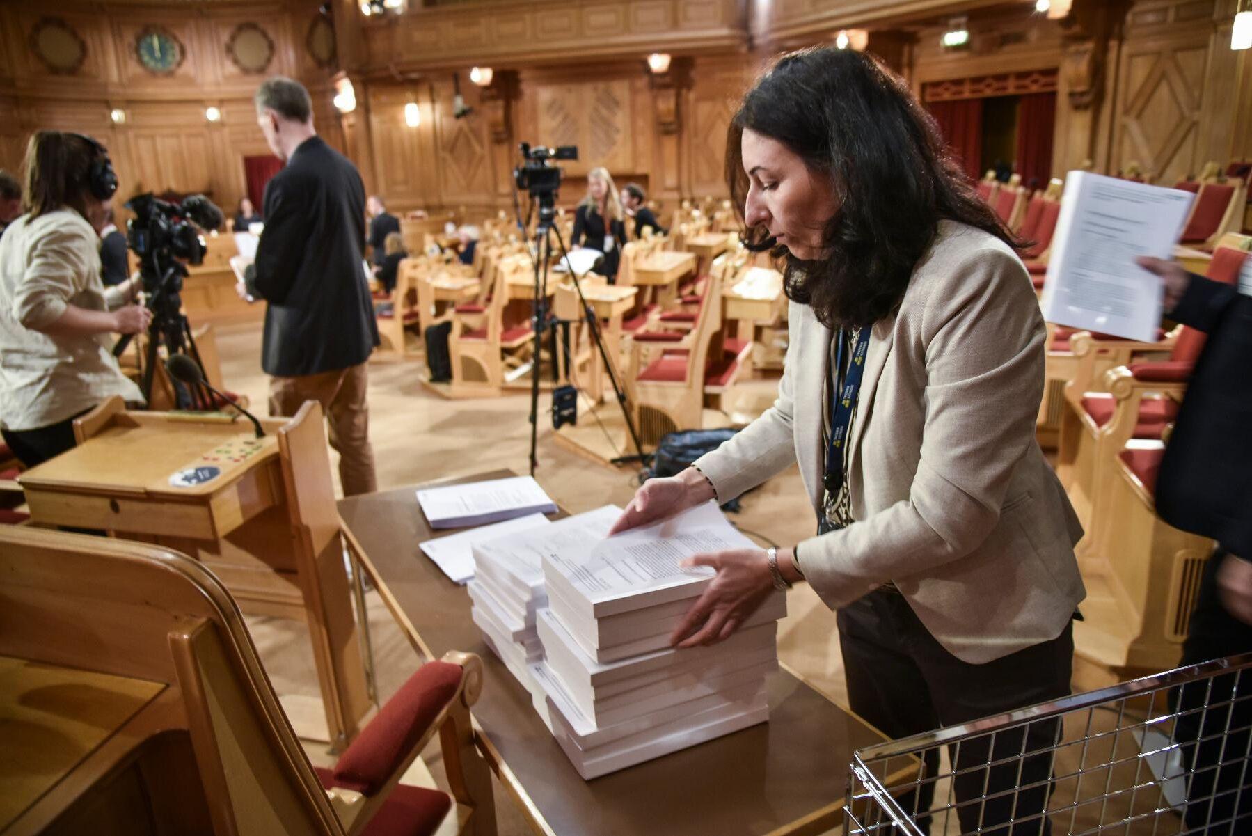 Konstitutionsutskottets granskningsbetänkande delas ut vid en pressträff i riksdagen. Mer än hälften av den rejäla luntan handlar om regeringens hantering av pandemin.