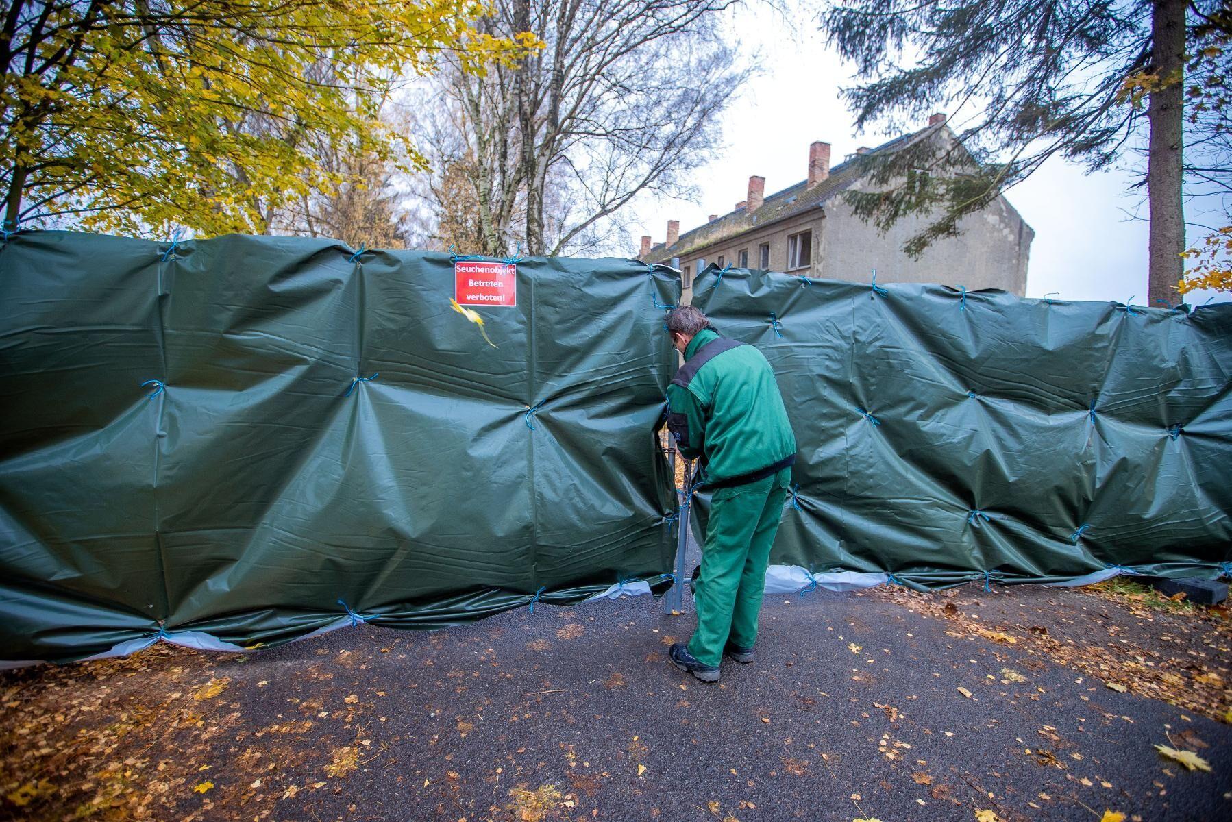 Stängslet runt en hönsuppfödning utanför Rostock i nordöstra Tyskland förstärks med en presenning efter ett utbrott av fågelinfluensa i mitten på november.