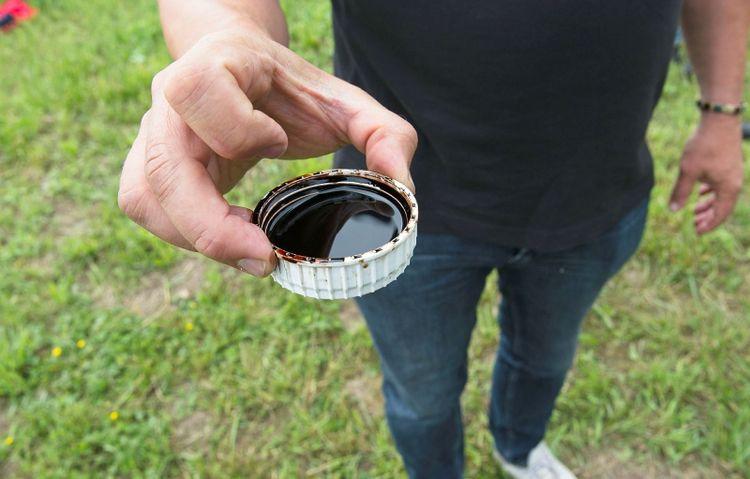 En man håller upp en brun vätska i en behållare – biostimulanten Stimplex från BioAgri.