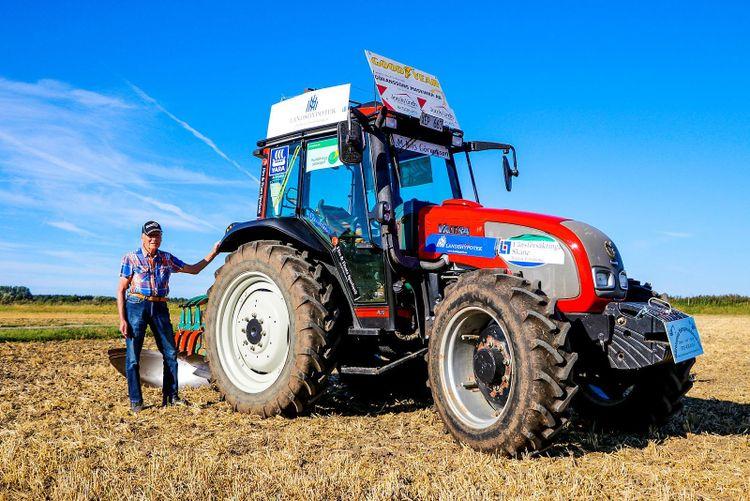 Man bredvid sin traktor Valtra A75 på åker.