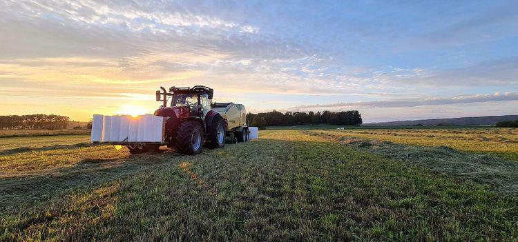 Traktorn är en Case IH 150 Maxxum och pressen är en Krone Comprima CV150XC Plus. Martin Knutsson har rejält med plast i fronten på traktorn.