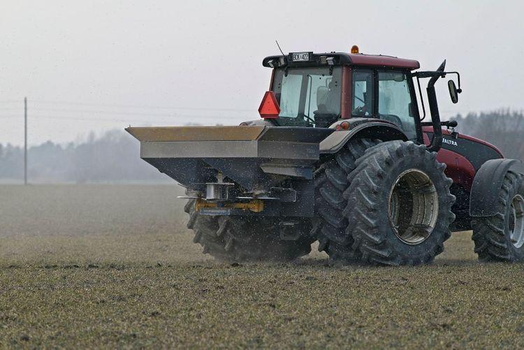 Traktor sprider mineralgödsel.