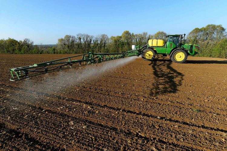 Traktor sprutar växtskyddsmedel på åker.