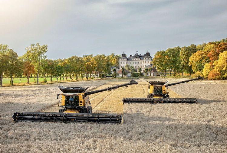 Wooow, vilken fantastisk skördebild! Det är Upplandsslätten och två New Holland 10.90 med 45 fots skärbord jobbar med Sjöö slott i bakgrunden. Fotograf är Mia Litström.