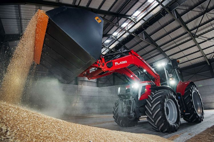 Traktor lastar spannmål.