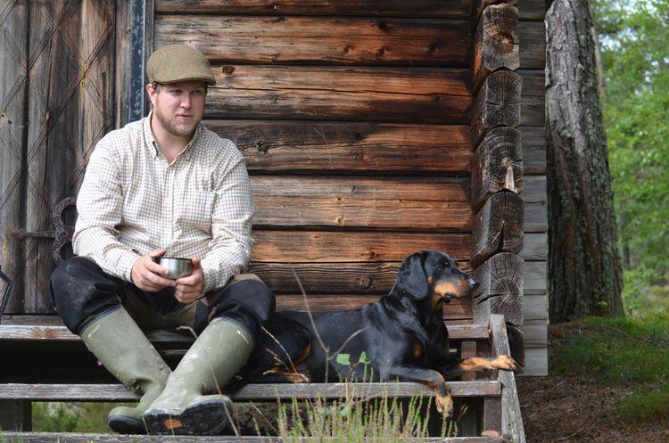 Jens Gustafsson sitter vid en timmerstuga med jakthund.