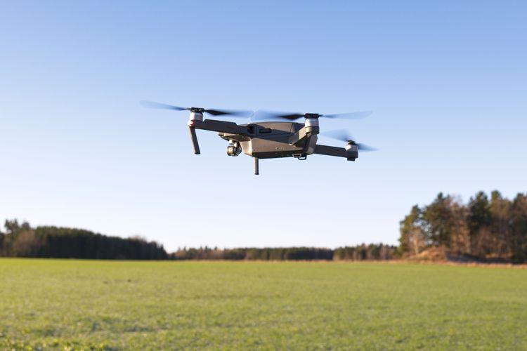 En drönare som flyger över fält.