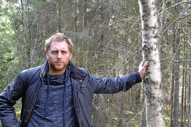 Mathias Mattsson står i skogen och lutar handen mot ett träd.