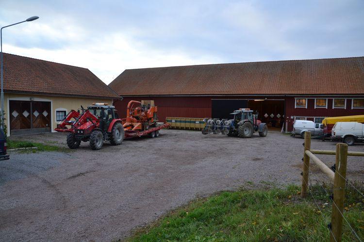 Gårdsplan med traktorer och ekonomibyggnader.