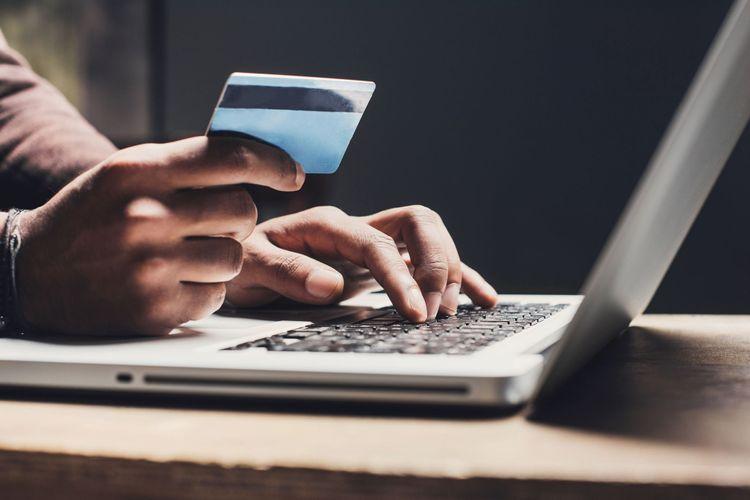 Närbild på hand som håller kreditkort och en laptop.