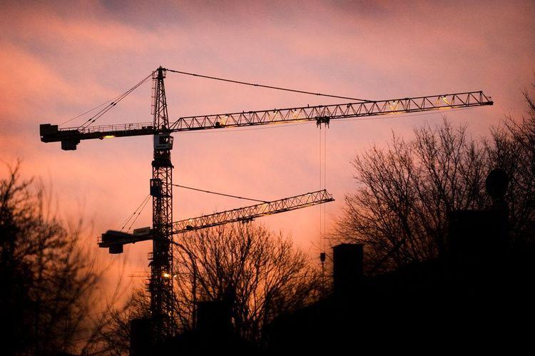 Två byggkranar i solnedgång.