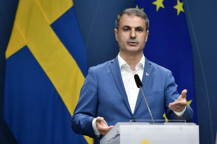 Näringsminister Ibrahim Baylan vid ett podium, framför en svensk flagga och en EU-flagga.