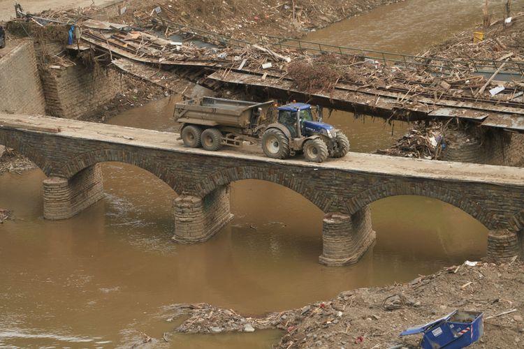 En traktor kör på en bro över en översvämmad flod.