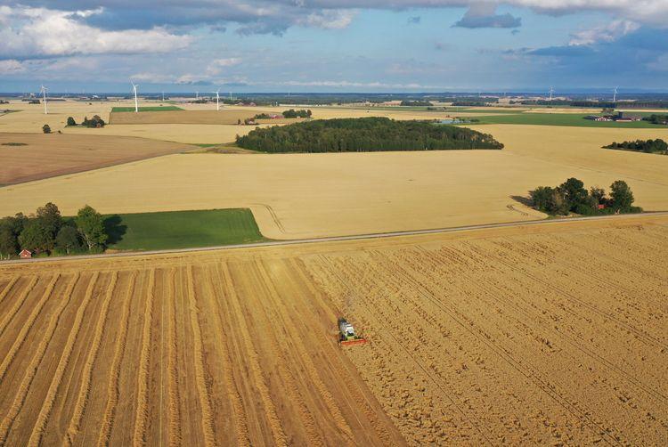 Flygbild på fält och tröska.