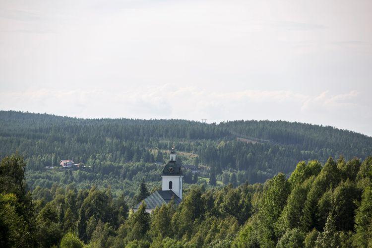 Kyrka omgiven av skog.