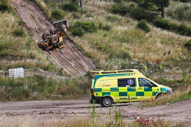 En ambulans står framför en lastmaskin som ligger upp och ner i en slänt.