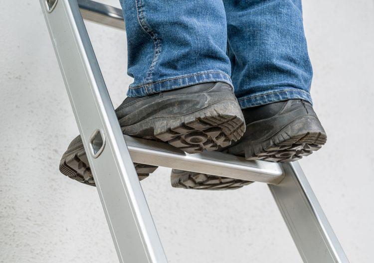 En person står på en stege, sett underifrån.