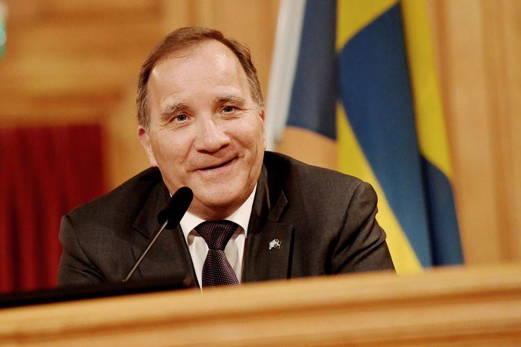 En leende Stefan Löfven sitter framför en mikrofon i riksdagen.