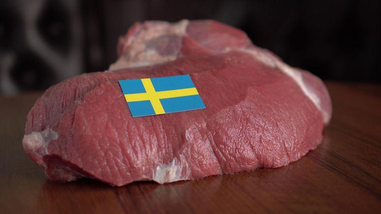 En bit rått kött med en svensk flagga i papper.